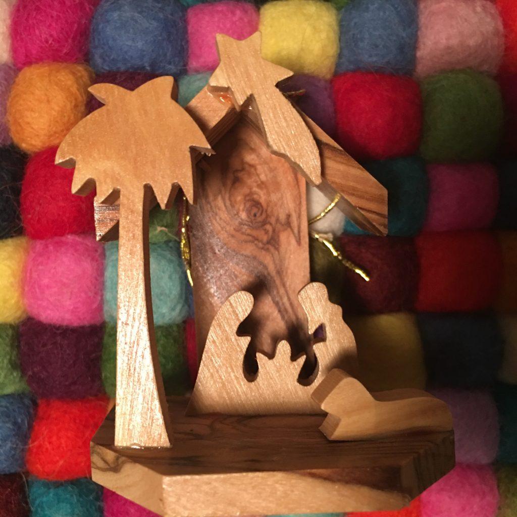 Pieni puinen seimiasetelma värikästä tekstiilitaustaa vasten. Kuvaaja Liina Pajunen.